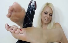 Blonde babe practicing a footjob on a big toy